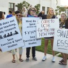 Students Hold Up Signs with Grievances