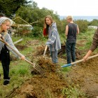 Students harvest the land to prepare for crops.
