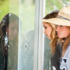 Isla Vista residents examine the bullet holes in the IV Deli Mart window on May 24. (Photo by Lorenzo Basilio)