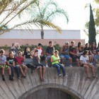 Students perched on a ledge as they enjoy Jack Johnson's performance.